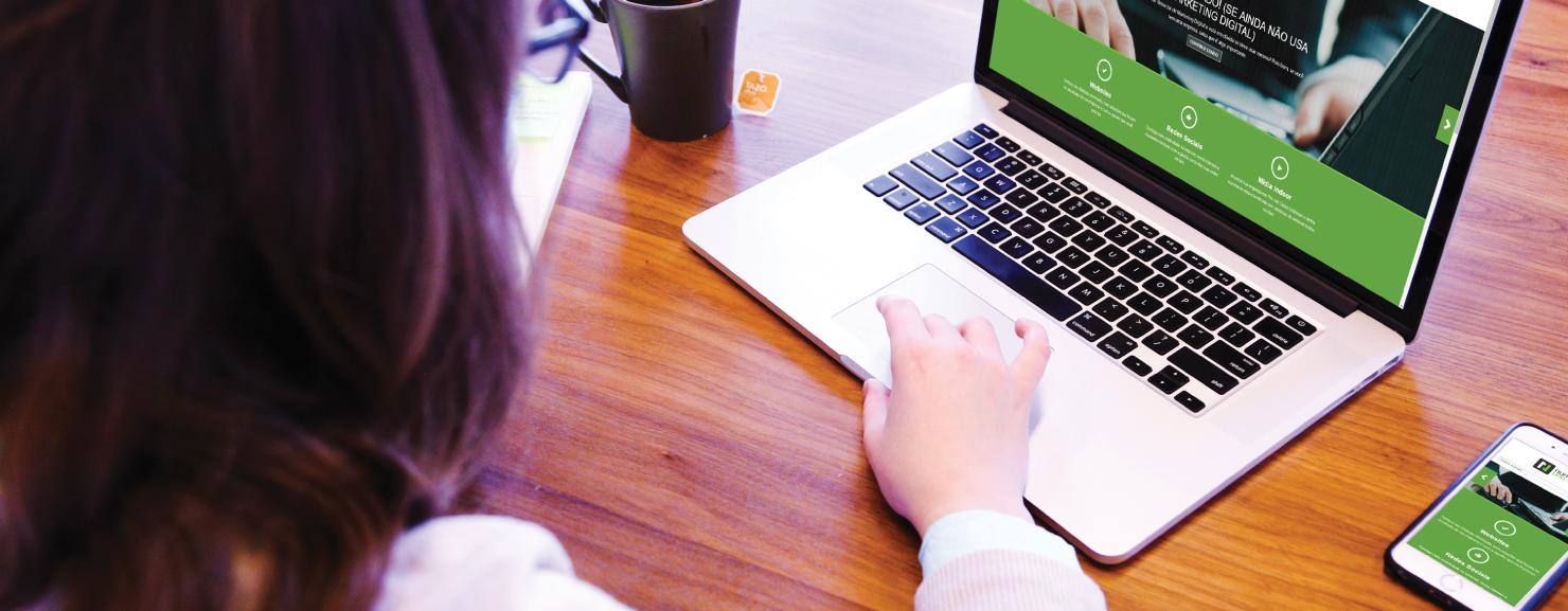 Uma mulher mexendo em um computador e a tela do site está adaptada ao computador e ao celular ao lado, exemplificando o que é site responsivo
